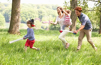young family playing pirates and running through grass with play swords