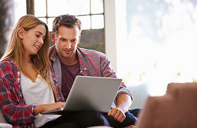young couple on couch looking at a laptop together