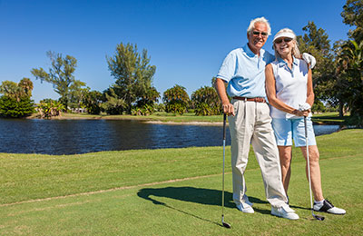 senior citizen man and woman smiling on golf course