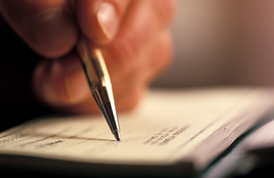 hand with pen writing in a check book