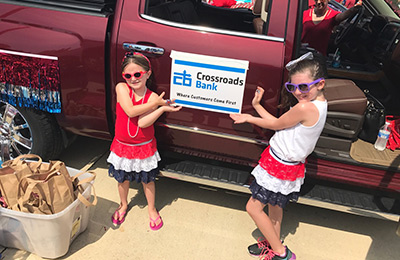 little girls standing next to truck with Crossroads Bank sign at the Dieterich 4th of July Parade