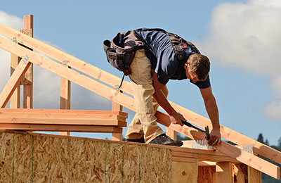 carpenter nailing rafters in place on a house