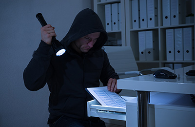 thief looking through a drawer full of papers