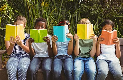 school children sitting down with books in front of their faces