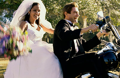just married couple riding off on motorcycle