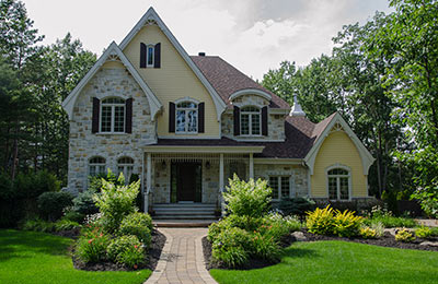 dream house with stone and yellow siding